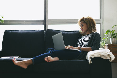 Young woman sitting on the couch using laptop - EBSF000878
