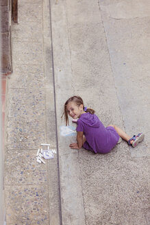 Smiling girl drawing with crayon on the street - XCF000006