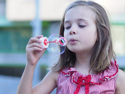 Portrait of little girl making soap bubble - XCF000010