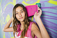 Portrait of teenage girl holding a skateboard in front of wall with graffiti - GEMF000362