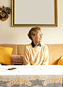Portrait of aged woman sitting on couch in her living room - MFRF000462