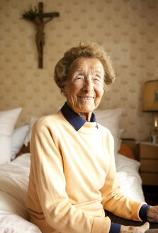 Portrait of aged woman sitting on bed at her bedroom - MFRF000470