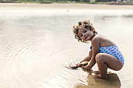 Portrait of smiling little girl wearing swim suit playing at seafront - MGOF000707