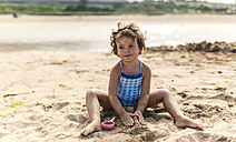 Portrait of smiling little girl wearing swim suit playing on the beach - MGOF000708