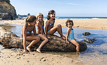 Spain, Colunga, four girls sitting on dead wood on the beach - MGOF000709