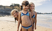 Spain, Colunga, three happy girls on the beach - MGOF000715