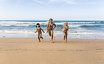 Spain, Colunga, three girls running side by side on the beach - MGOF000719