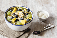 Bowl of green smoothie and fruits sprinkled with coconut flakes - EVGF002255
