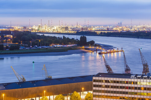 Belgium, Flanders, Antwerp, View to dock area with industrial area at Scheidt river in the evening - WDF003279