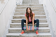 Portrait of happy teenage girl with colorful skateboard sitting on stairs - GEMF000378