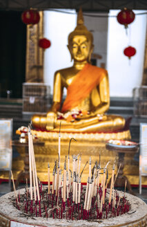 Thailand, Bangkok, vessel with burnt down joss sticks with golden Buddha statue in the background - EH000217