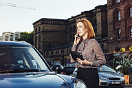 Portrait of businesswoman with file standing beside parked car telephoning - TAM000312