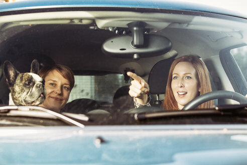 Two female friends sitting in a car with their French bulldog - TAM000308