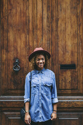 Spain, Barcelona, portrait of smiling young woman wearing hat and denim shirt standing in front of wooden door - EBSF000912