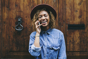 Spain, Barcelona, portrait of smiling young woman telephoning in front of wooden door - EBSF000915