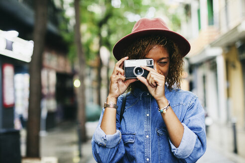 Spain, Barcelona, portrait of smiling young woman wearing hat and denim shirt taking picture with camera - EBSF000916