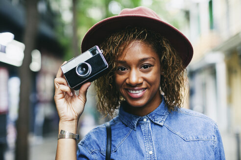 Portrait of smiling young woman wearing hat and denim shirt holding camera - EBSF000918