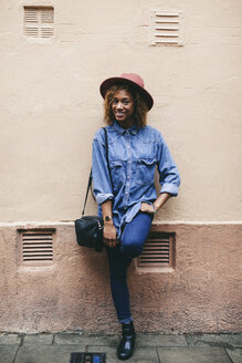 Portrait of smiling young woman wearing hat and denim shirt standing in front of house facade - EBSF000921