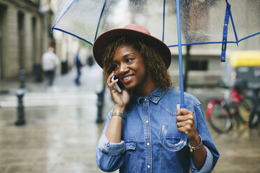 Spain, Barcelona, portrait of smiling young woman with umbrella and smartphone - EBSF000922
