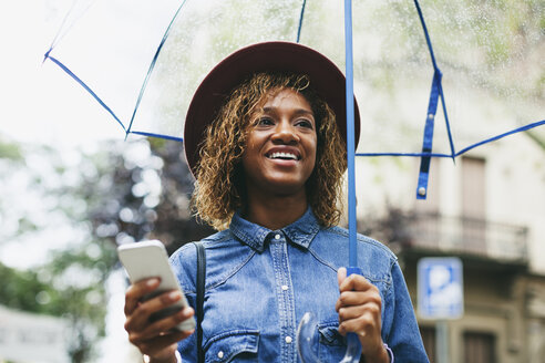 Spain, Barcelona, portrait of smiling young woman with umbrella and smartphone - EBSF000924