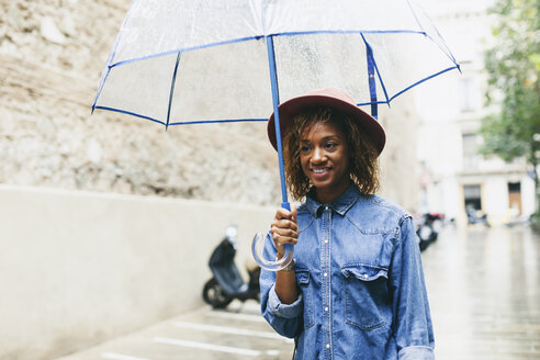 Spain, Barcelona, portrait of smiling young woman with umbrella wearing hat and denim shirt - EBSF000933