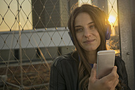 Portrait of smiling young woman with closed eyes hearing music with headphones at backlight - RIBF000317