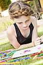 Girl lying on a meadow with colouring book and felt tip pens - JUNF000432