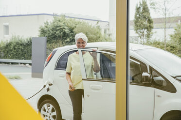 Mature woman charging electric car - MFF002229
