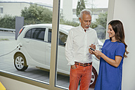 Man and woman talking while charging electric car, woman holding key - MFF002217
