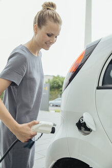 Young woman charging electric car - MFF002220