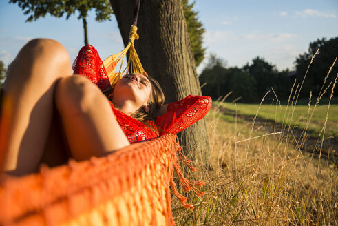 Smiling woman relaxing in a hammock in nature - UUF005656