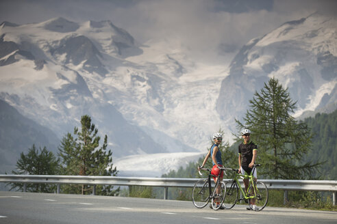 Switzerland, Engadin, two cyclists on Bernina Pass road in front of Morteratsch Glacier - FF001458