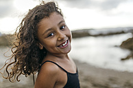 Spain, Gijon, portrait of smiling little girl on the beach - MGOF000737
