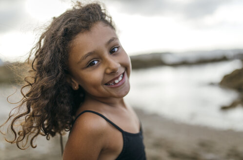 Spain, Gijon, portrait of smiling little girl on the beach - MGOF000737