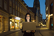 Germany, Muenster, portrait of young woman with laptop in the city at evening - TAM000294