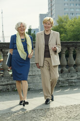 Germany, Berlin, portrait of two smiling senior businesswomen with laptop and smartphone - TAM000323