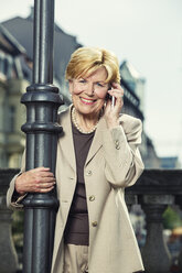 Germany, Berlin, portrait of smiling senior businesswoman telephoning with smartphone - TAM000327