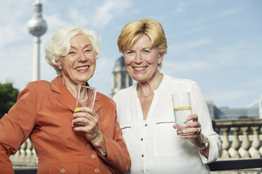 Germany, Berlin, portrait of two smiling senior women with glasses of mineral water - TAMF000334