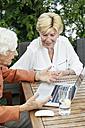 Germany, Berlin, two senior women using laptop - TAMF000335