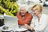 Germany, Berlin, portrait of two laughing senior women looking at laptop - TAMF000336