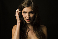 Portrait of brunette young woman in front of black background - SHKF000366