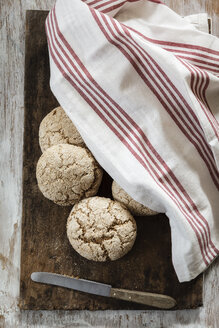 Homemade rye bread rolls on chopping board, kitchen towel - EVGF002431