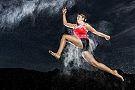 Young woman jumping in the air in flour dust cloud - STSF000921