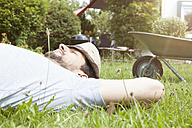 Man lying on lawn relaxing from gardening - RBF003151