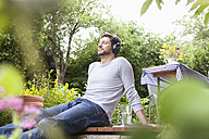 Relaxed man sitting in garden with headphones - RBF003155