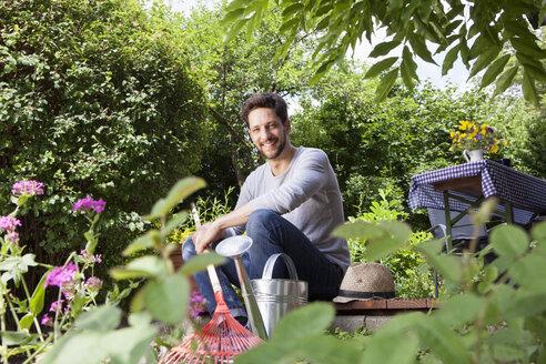 Smiling man sitting on garden terrace - RBF003158