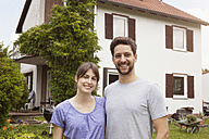 Portrait of smiling couple in garden in front of residential house - RBF003166