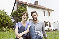 Portrait of smiling couple in garden in front of residential house - RBF003169