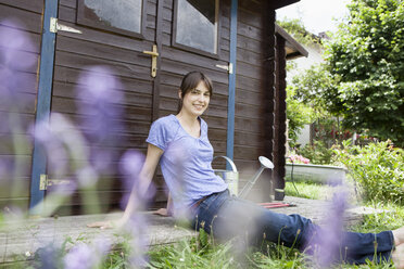Smiling woman sitting at garden shed - RBF003206