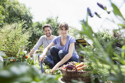 Smiling couple gardening in vegetable patch - RBF003209